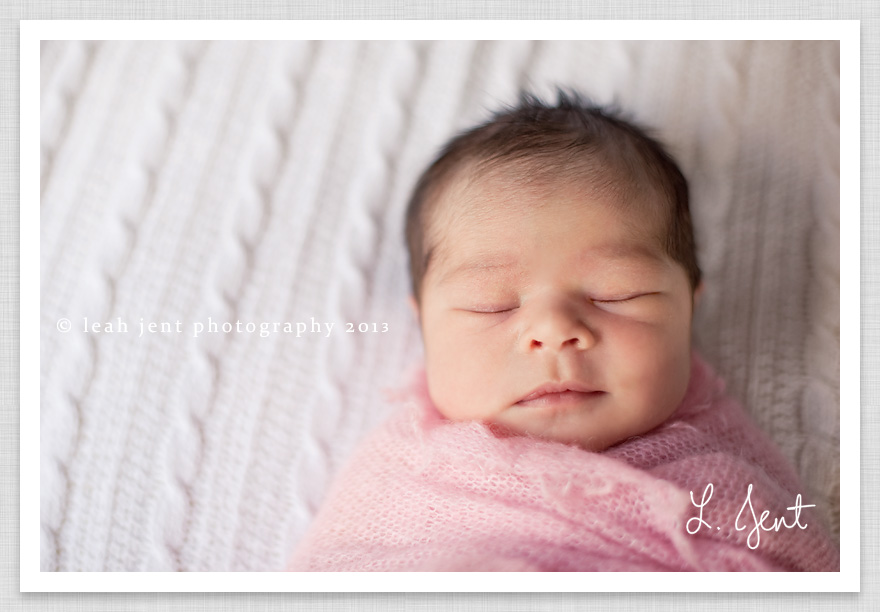 newborn girl in pink wrap